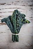 A bundle of black kale on a wooden surface