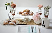 Croissants with icing sugar on a cake stand between vases of flowers