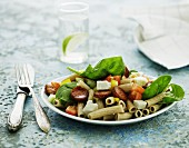Pasta salad with sausage, tomatoes, feta cheese and spinach