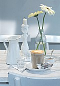 Cafe latte and sugar on a white wooden table with candle holder and a vase of flowers
