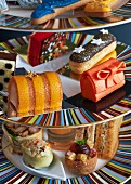 Sandwiches and sweet pastries on a cake stand for teatime (close-up)