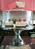 Himbeerkuchen auf Kuchenständer mit Glashaube zur Teatime im Restaurant