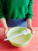 A woman holding a mixing bowl with a spatula