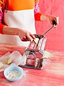 Crackers being made: a woman putting cracker dough through a pasta machine