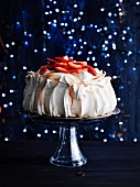 Strawberry pavlova against a glittery blue background