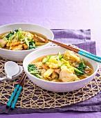 Asiatische Suppe mit Hähnchen-, Schweinefleisch und Garnelen