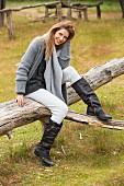 Junge Frau in grauer Strickkleidung und Lederstiefeln sitzt auf Baumstamm