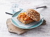 An oat roll with a carrot and sesame seed spread