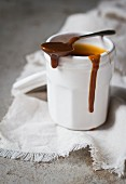 Salted caramel sauce in a cot with a spoon