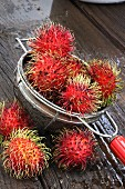 Rambutans in a sieve on a wooden surface