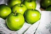 Grüne Äpfel mit Wassertropfen auf Geschirrtuch