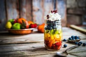 A colourful fruit salad in a jar topped with cream and pomegranate seeds on a rustic wooden surface