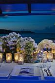 Windlichter und Blumensträusse auf festlich gedecktem Hochzeitstisch in Abendstimmung