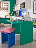 Kleines Appartement mit platzsparendem grünem Frühstückstisch, passender Wandfarbe und blauem Holzhocker