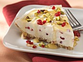 A slice of cranberry pie with pistachio nuts and honey