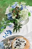 Blau-weisser Gartenblumenstrauß mit Blaubeertörtchen
