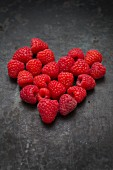 Raspberries arranged in a heart shape on a metal surface