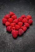 Raspberries arranged in a heart shape on a metal surface