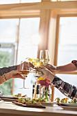 Hände stossen mit Weingläsern an