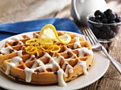 A round blueberry waffle with vanilla sauce and lemon zest
