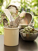 Kitchen utensils and artichokes in a stainless steel