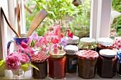 Verschiedene Marmeladengläser beim Küchenfenster