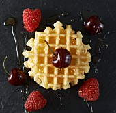 A Belgian waffle with fruit and maple syrup