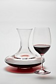 A glass carafe and a glass of red wine on a white surface
