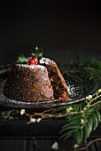 Christmas pudding decorated with holly, sliced