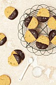 Pistachio biscuits dipped in dark chocolate and sprinkled with sea salt on a wire rack