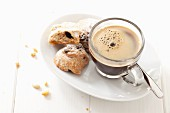 Black coffee in a glass cup on a saucer served with pine nut biscuits (Italy)