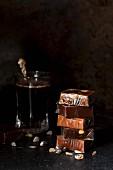 Gestapelte Karamellbonbons, in Cellophan verpackt, neben Kaffeeglas
