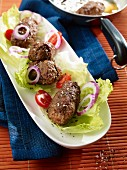 Cevapcici with onions, tomatoes and lettuce