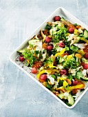 A colourful salad with avocado, peppers, fish and raspberries
