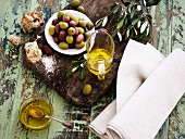 An arrangement of oils with olive oil, olives, bread and salt