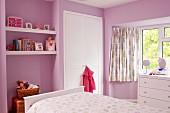 Rosa getöntes Kinderzimmer, Blick über Bett auf Nische mit eingespannten Ablagen und weisser Einbauschank, seitlich Kommode vor Fenster