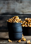 Caramelised popcorn in a stack of bowls