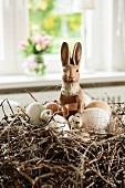 Hare figurine and eggs in Easter nest made from willow twigs