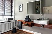 Massgefertigte Waschtischablage mit Porzellanwaschbecken, oberhalb Spiegel an hellgrauer Wand