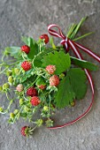 A bouquet of wild strawberries on a slate surface