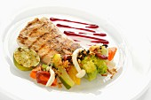 Grilled fish fillet with a vegetable salad, chilli sauce and lime