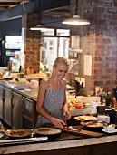Frau bei der Speisenzubereitung im Restaurant