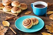 Cinnamon bun on a plate with a cup of tea