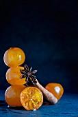 Kandierte Clementinen mit Sternanis und Zimtstangen auf blauem Schiefer
