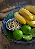 An exotic arrangement of bananas, limes and cashew nuts