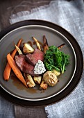 Roast beef on a bed of oven-roasted vegetables