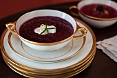 Borscht in an elegant porcelain soup cup with a golden rim