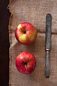 Two apples with an antique knife on a piece of sack (seen from above)