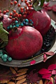 Pomegranates with autumnal sprigs of berries on a pewter plate