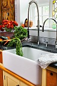 Fresh vegetables and flowers next to a sink with a modern tap in a farmhouse kitchen